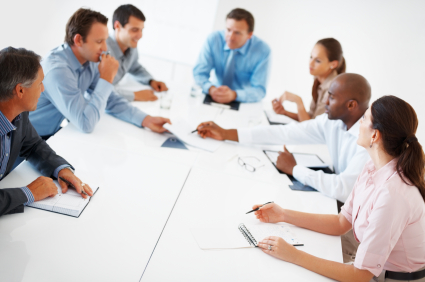 Group of executives sitting in board room during meeting and discussing with paperwork